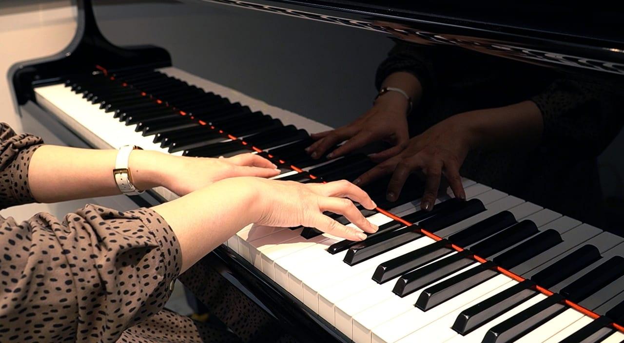 グランドピアノを弾く女性